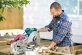 Carpenter cutting wood using table saw at happy mid adult construction site Stock Images