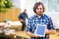 Carpenter displaying digital tablet with coworker mid adult working in background at construction site Royalty Free Stock Photo