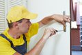 Carpenter at door lock installation male handyman worker interior wood or repairing Royalty Free Stock Image