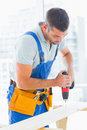 Carpenter drilling hole in plank in office male bright Royalty Free Stock Images