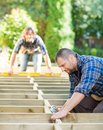 Carpenter drilling wood with coworker in mid adult background at construction site Stock Photos