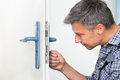 Carpenter Fixing Lock In Door With Screwdriver Royalty Free Stock Photo