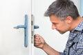 Carpenter Fixing Lock In Door With Screwdriver Royalty Free Stock Photo