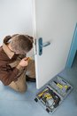 Carpenter fixing lock with screwdriver high angle view of male door Stock Image