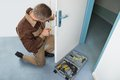 Carpenter fixing lock with screwdriver high angle view of male door Stock Photography