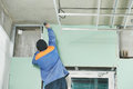 Carpenter with gypsum plasterboard and screwdriver joiner plasterer mounting system at toilet Royalty Free Stock Photography