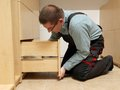 Carpenter installing wardrobe drawers in walk in closet Stock Image