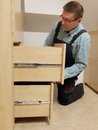 Carpenter installing wardrobe drawers in walk in closet Royalty Free Stock Photos