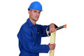 Carpenter posing with plank of wood and hammer Royalty Free Stock Image