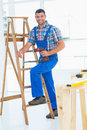 Carpenter with power drill climbing ladder at construction site Royalty Free Stock Photo