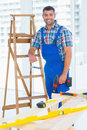 Carpenter with power drill standing by ladder at construction site Royalty Free Stock Photo
