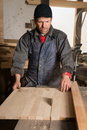 Carpenter sawing a board in the circulation saw s workshop Stock Photography
