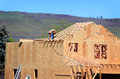 Carpenter setting trusses a with a nail gun wearing leather nail bags working on a roof of a house that is under construction Stock Image