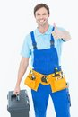 Carpenter showing thumbs up sign while carrying tool box Royalty Free Stock Photo