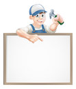 Carpenter sign a or builder holding a claw hammer and peeking over a and pointing Stock Images