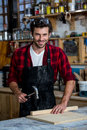 Carpenter smiling and working on his craft the workshop Stock Image