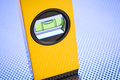 Carpenter spirit level instrument a yellow also known as a bubble photographed over a perforated metal background Royalty Free Stock Image
