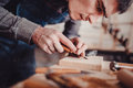 Carpenter use a chisel to shapes a wooden plank. Royalty Free Stock Photo