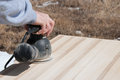 A carpenter uses a hand held random orbit power sander to smooth a hand crafted table top Royalty Free Stock Photo