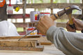 Carpenter using  chisel and hammer in his hand with plank.Close up Royalty Free Stock Photo