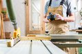 Carpenter using electric saw in carpentry working on an buzz cutting some boards Royalty Free Stock Photo