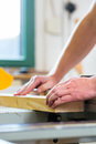 Carpenter using electric saw in carpentry working on an buzz and cutting some boards Stock Photo