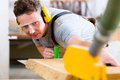 Carpenter using electric saw in carpentry working on an buzz cutting some boards he is wearing safety glasses and hearing Royalty Free Stock Images