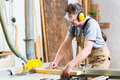 Carpenter using electric saw in carpentry working on an buzz cutting some boards he is wearing safety glasses and hearing Stock Photography