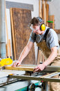 Carpenter using electric saw in carpentry working on an buzz cutting some boards he is wearing safety glasses and hearing Stock Image