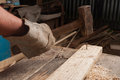 Carpenter using a hammer hitting a nail on wood male big in his workshop Stock Images