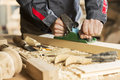 Carpenter at work close up of hands working with plane in his studio Royalty Free Stock Photos