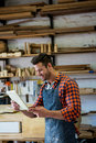 Carpenter working on his craft in a dusty workshop Royalty Free Stock Image