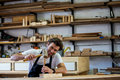 Carpenter working on his craft in a dusty workshop Royalty Free Stock Photography