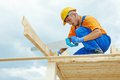 Carpenter works with hand saw construction roofer worker sawing wood board on roof installation work Royalty Free Stock Images