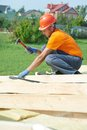 Carpenter works on roof construction worker nailing wood board with hammer installation work Royalty Free Stock Images