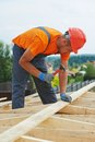 Carpenter works on roof construction worker nailing wood board with hammer installation work Stock Images