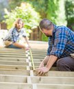 Carpenters measuring wood with tape at site mid adult construction Royalty Free Stock Images