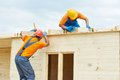 Carpenters at wooden roof work two construction roofers workers installing wood board Royalty Free Stock Photos