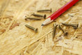 Carpentry concept close up of pencil and screws on wooden board Royalty Free Stock Photography