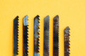 Carpentry saw blade teeth set. Rusty textured woodworking instrument on yellow paper background, shallow depth of field