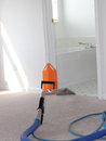 Carpet cleaning in progress a being performed by professional company orange corner guard keeps scratches and dings from fine Stock Image