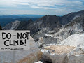 Carrara marble quarries view and sign no climbing in foreground big drop in background warning for tourists Stock Photos