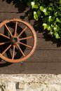 Carriage wheel hangs on board wall Stock Image