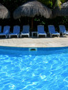 Carribean resort with poolside chairs Royalty Free Stock Photo