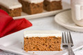 Carrot cake on a white plate with fork shallow depth of field tea cup saucer Royalty Free Stock Image