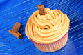 Carrot and cinnamon cupcake on a glass dish over a blue background Royalty Free Stock Photography