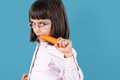 Carrot is good for vision cute little girl with glasses biting a concept of vitamins Royalty Free Stock Image