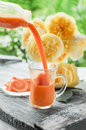 Carrot juice is poured from a jug into a glass Cup on a background of roses.