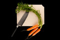 Carrot with knife carrots on wooden cutting board on black background Stock Images