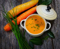Carrot soup on wooden background Royalty Free Stock Photography